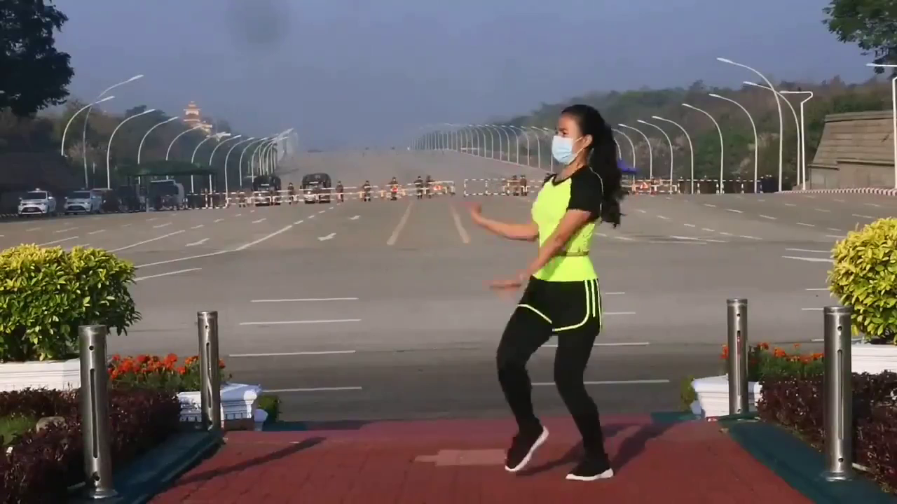 A woman conducted her aerobics class in Myanmar without realizing a coup was taking place. Behind her, a military convoy arrives at parliament.