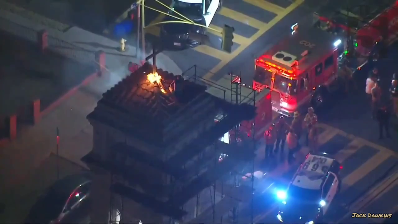 A man has scaled a church in Los Angeles and set fire to the cross above