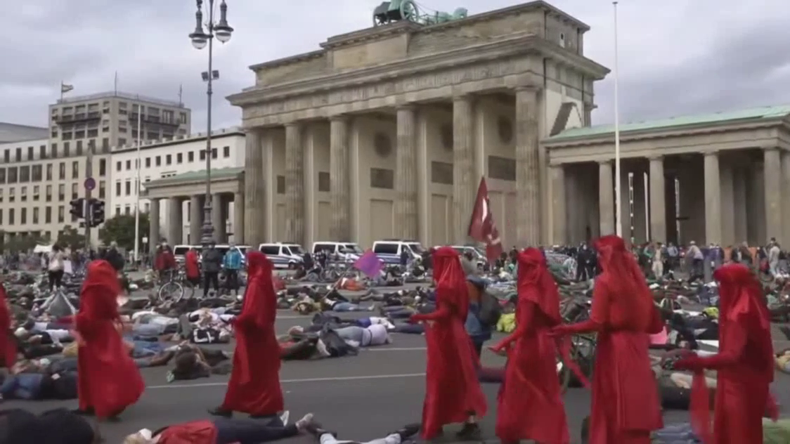 """bLASPHEMY !! Extinction Rebellion """"climate cultists"""" walk past the Brandenburg Gate as they occupy a street in Berlin, Germany."""
