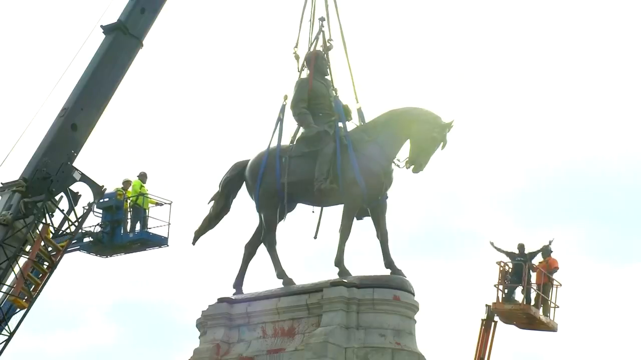 Robert E. Lee statue, erected in 1890 and the largest Confederate Monument in the U.S., is removed in Richmond as the crowd frenetically cheers the moment.